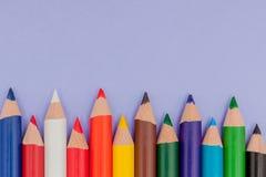 Colori le matite su fondo viola per i progetti e gli annunci immagini stock