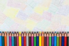 Colori le matite in una fila con fondo variopinto Immagine Stock Libera da Diritti