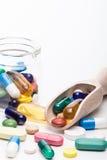 Colori le pillole in contenitore di vetro e ritratto di legno del dispencer Immagine Stock