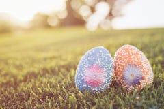 Colori le uova su erba verde con il bokeh della sfuocatura e il backgroun di luce solare Immagine Stock Libera da Diritti