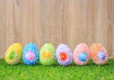 Colori le uova su erba verde con il fondo di legno della parete Per Easte Fotografia Stock Libera da Diritti