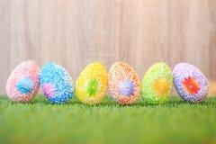 Colori le uova su erba verde con il fondo di legno della parete Per Easte Fotografia Stock