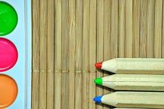 Colori luminosi degli acquerelli, matite di legno Superficie del bambù fotografia stock libera da diritti