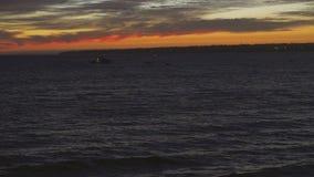 Colori stupefacenti del tramonto Siluette delle barche a vela che galleggiano sull'orizzonte dell'oceano stock footage