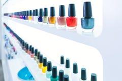 Colori variopinti dello smalto in una fila al salone delle unghie su bianco Fotografia Stock