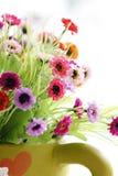 Coloridas son las flores en un florero verde. Imagen de archivo libre de regalías