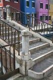 Colorido casas marrons, azuis, cor-de-rosa, amarelas com a ponte com os trilhos do metal em Burano Veneza Itália fotos de stock