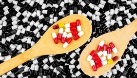 Colorido de antibióticos encapsule las píldoras en cuchara de madera Imágenes de archivo libres de regalías