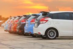 Colorido de coches en el estacionamiento en fondo de la puesta del sol fotos de archivo