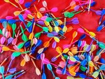Colorido de muchos dardos en fondo rojo imagen de archivo