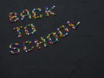 Colorido DE NUEVO a palabras de la ESCUELA con la parte de extremidades del lápiz del color mostradas en el marco Concepto de nue Foto de archivo