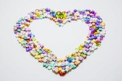 Colorido dos grânulos com forma do coração Fotografia de Stock Royalty Free
