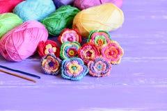 Colorido fazer crochê as flores ajustadas Brilhante fazer crochê flores, fio de algodão varicolored, agulhas de crochê no fundo d Fotos de Stock