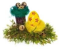 Colorido pintado à mão dos ovos da páscoa no ninho do pássaro, musgo da floresta, Foto de Stock
