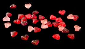 Colorido (rosa, vermelho e alaranjado), geleias transparentes da forma do coração, fundo preto Imagem de Stock Royalty Free