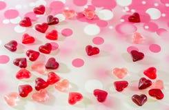 Colorido (rosa, vermelho e alaranjado), geleias transparentes da forma do coração, fundo colorido do degradee Fotografia de Stock