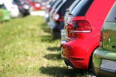 Coloridos aparcamiento en la hierba Automóviles rojos y verdes fotos de archivo