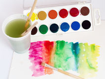 Coloring. Set of water colors, water, brushes and paper on white background Stock Images