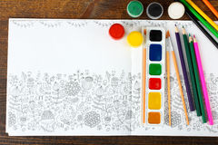 Coloring antistress. Colorer - antistress with colored pencils and watercolor brushes on the wooden brown table Royalty Free Stock Photography