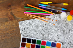 Coloring antistress. Colorer - antistress with colored pencils and watercolor brushes on the wooden brown table Royalty Free Stock Photo