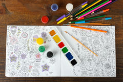 Coloring antistress. Colorer - antistress with colored pencils and watercolor brushes on the wooden brown table Stock Image