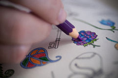 Coloring book. Closeup image of adult person drawing on coloring book with color pencil stock photography