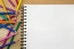 Coloring colored pencils next to sketch drawing book on wooden b. Top view of coloring colored pencils next to sketch drawing book on wooden background stock photos