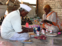 Coloring Diwali. An poor elder Indian couple coloring the idols specially made for diwali festival in India in their home Royalty Free Stock Photos
