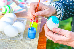 Coloring Easter egg. In hands Stock Photo