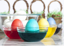 Coloring Easter Eggs. Four eggs in glass bowls of dye, one red, one turquoise, one yellow and one blue. White eggs in large glass bowl and Easter baskets blurred royalty free stock images