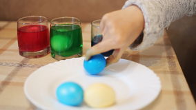 Coloring eggs in bright colors stock footage