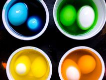 Coloring eggs. White colored cans with paint for coloring objects at home at black background. Easter eggs coloring and painting Stock Photo