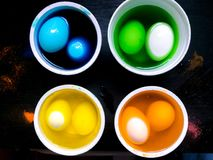 Coloring eggs. White colored cans with paint for coloring objects at home at black background. Easter eggs coloring and painting Royalty Free Stock Images