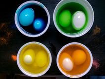 Coloring eggs. White colored cans with paint for coloring objects at home at black background. Easter eggs coloring and painting Stock Photos