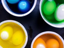Coloring eggs. White colored cans with paint for coloring objects at home at black background. Easter eggs coloring and painting Stock Image