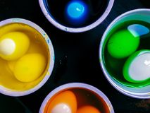 Coloring eggs. White colored cans with paint for coloring objects at home at black background. Easter eggs coloring and painting Stock Images