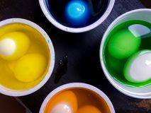 Coloring eggs. White colored cans with paint for coloring objects at home at black background. Easter eggs coloring and painting Royalty Free Stock Image
