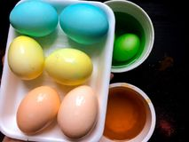 Coloring eggs. White colored cans with paint for coloring objects at home at black background. Easter eggs coloring and painting Stock Photography
