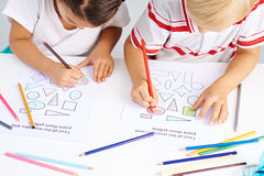 Coloring figures. Preschoolers coloring different figures in classroom royalty free stock photos