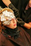 Coloring hair with foil. Beautiful woman having hair colored with foil in a salon Stock Images