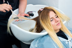 Coloring hair preparation. Attractive woman in hair salon with coloring foil on her head and washing Royalty Free Stock Images