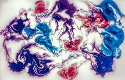 Coloring ink flowing and mixing in milk texture. Top view Stock Photo