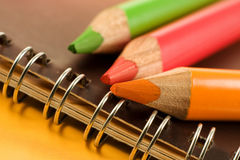 Coloring Leads. Bright and colorful coloring pencils, green, red and orange on notebook - closeup Stock Photos