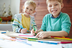 Coloring at leisure. Two brothers coloring pictures with highlighters Stock Image