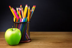 Coloring pencil and apple. Pot of coloring pencils and green apple of wooden desk, educational concept Stock Image