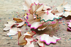 Coloring pencil shavings on wooden desk background. Nn royalty free stock image
