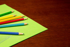 Coloring Pencils on Desk. Coloring Pencils and Colored Paper on Desk Royalty Free Stock Photography