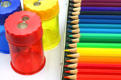 Coloring pencils and  pencil sharpeners. A box of coloring pencils and some pencil sharpeners Stock Images