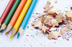 Coloring pencils and pencil shavings on notebook. Background Royalty Free Stock Photography