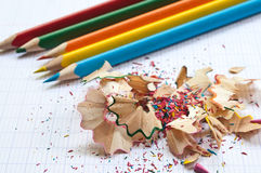 Coloring pencils and pencil shavings on notebook. Background Stock Photo